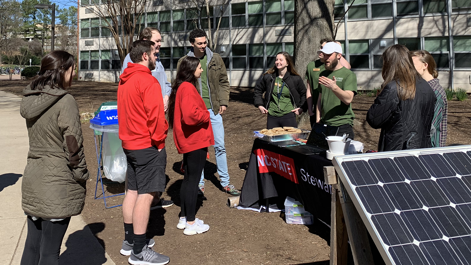 NC State Stewards, wearing matching green T-shirts, speak to a small group of fellow students outside next to a solar panel - Finding Your Wolfpack: Floursih With Sustainability - Forest Biomaterials NC State University