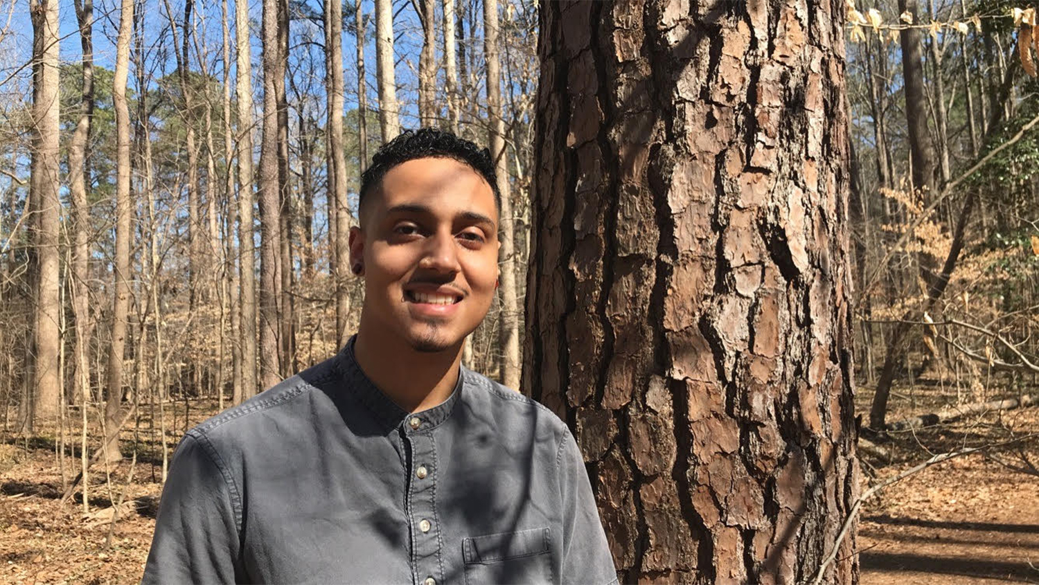 Norman poses and smiles in woods - Forestry Student Overcomes Challenges to Shine as Research Assistant - Forestry and Environmental Resources NC State University