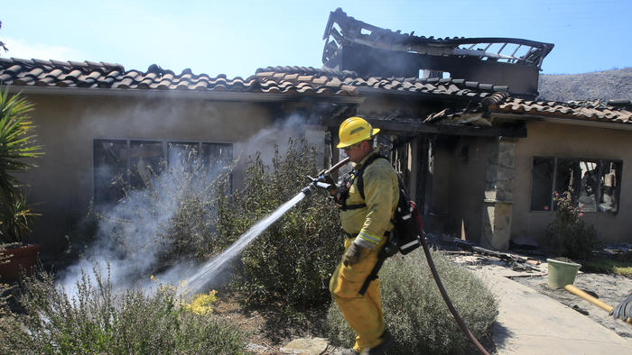 Firefighters douse final hotspots at David and Sherri Roberts home that was destroyed by fire 24-hours earlier on a hilltop in Escondido (LA Times)
