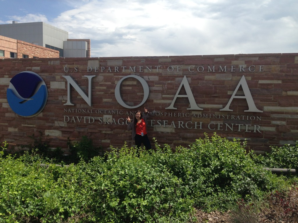 Deanna Metivier in front of the NOAA Climate Change Research Center sign in Boulder, CO.