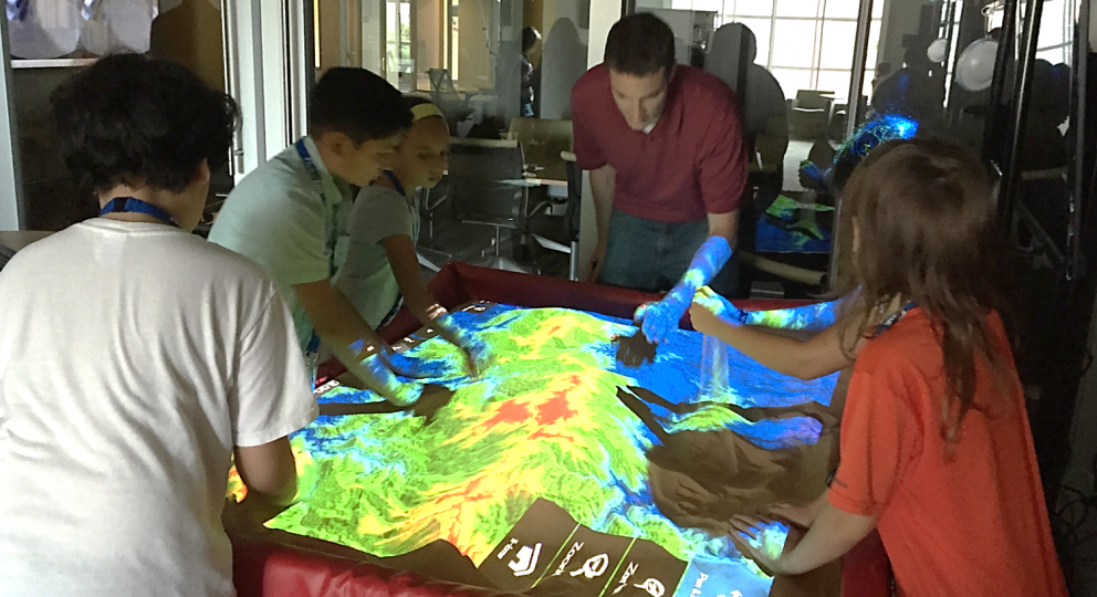 A photo of visiting students from a Duke Talent Identification Program (TIP) workshop at the North Carolina State University Center for Geospatial Analytics
