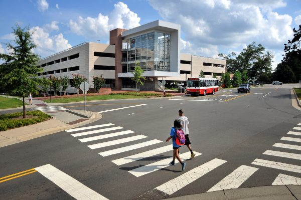 A photo of a Wolfline bus stopped at the West Parking Deck while students cross Varsity Drive at North Carolina State University