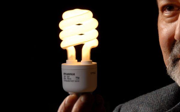 A photo of a man holding a CFL lightbulb