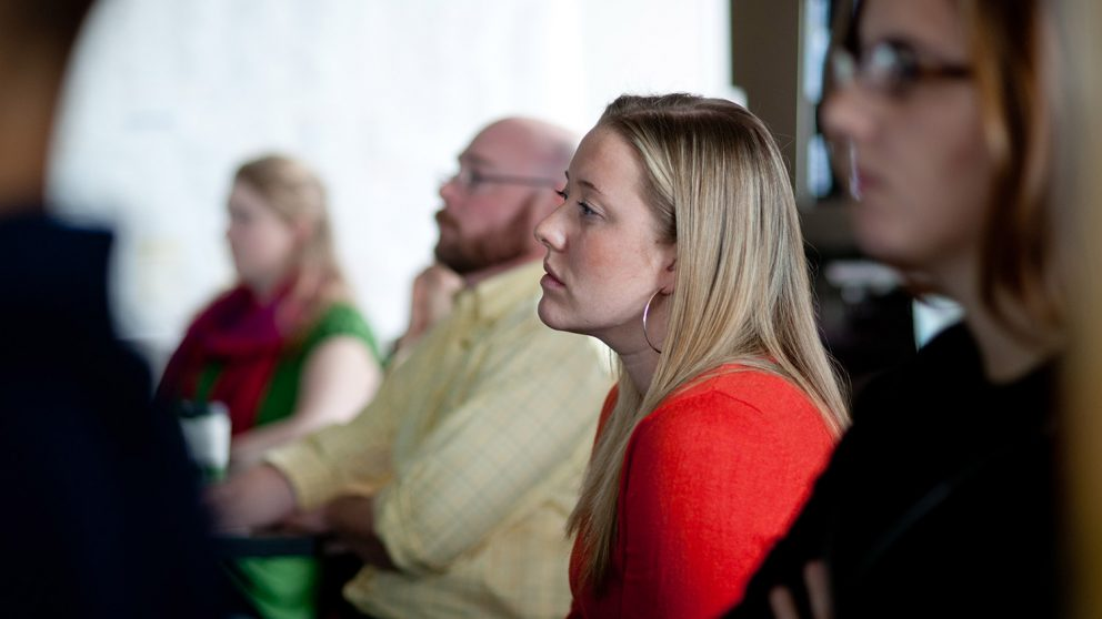 A woman listening to a lecture at the North Carolina State University Center for Geospatial Analytics