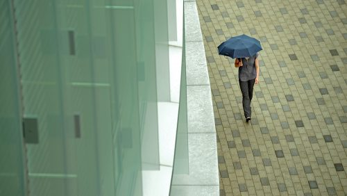 Student walking in the rain with an umbrella