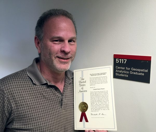 Paul Schrum holding his newly granted patent at the North Carolina State University Center for Geospatial Analytics