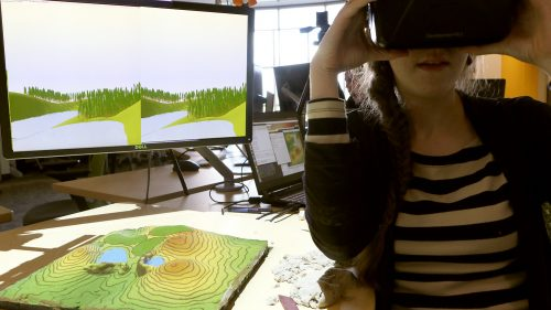 A student using an immersive virtual environment and the Tangible Landscape in tandem at the North Carolina State University Center for Geospatial Analytics