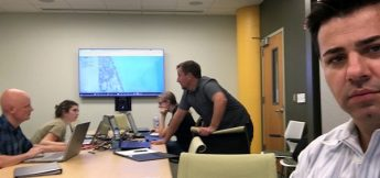 Okan Pala looks on as students collaborate during a simulated drill in a disaster management class at the North Carolina State University Center for Geospatial Analytics