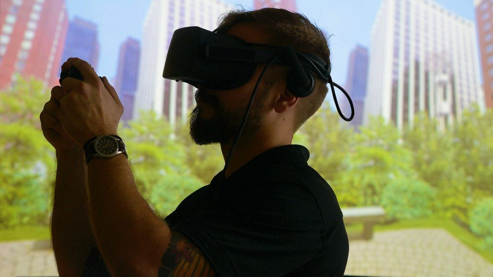 A photo of a user wearing an Oculus virtual reality headset at the North Carolina State University Center for Geospatial Analytics