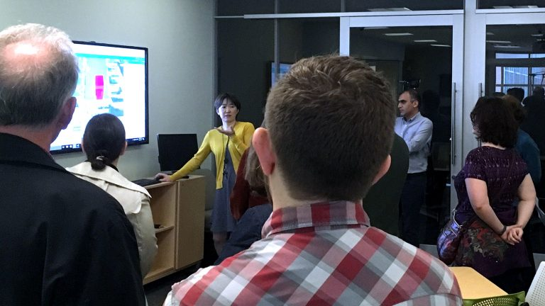 A photo of Makiko Shukunobe displaying a 3D web model at the North Carolina State University Center for Geospatial Analytics