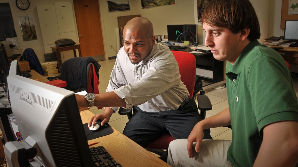A photo of Stacy Nelson working with a graduate student at the North Carolina State University Center for Geospatial Analytics