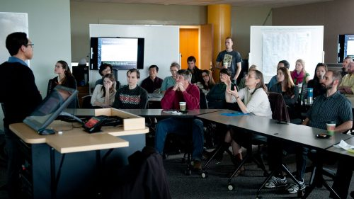 A photo of an audience at a presentation in an experimental classroom at the North Carolina Center for Geospatial Analytics
