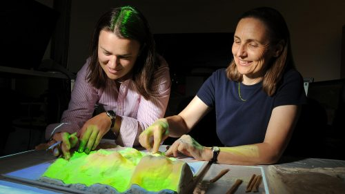 A photo of Helena Mitasova and a graduate student working with a 3D model of Jockey's Ridge