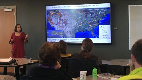 A photo of Stacy Supak giving a presentation at the A photo of a user wearing an Oculus virtual reality headset at the North Carolina State University Center for Geospatial Analytics