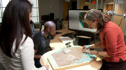 A photo of scholars using the Tangible Landscape at the North Carolina Center for Geospatial Analytics
