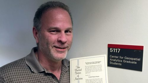 A photo of Master of Geospatial Information Science and Technology student Paul Schrum at the North Carolina State University Center for Geospatial Analytics after he was awarded a patent for improving roadway design