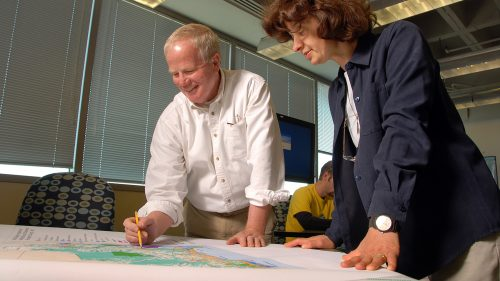 A photo of Hugh Devine and Perver Baran standing over a map at the North Carolina State University Center for Geospatial Analytics