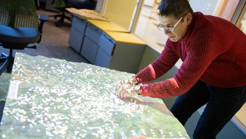 A photo of a man using a modeling tool at the North Carolina State University Center for Geospatial Analytics