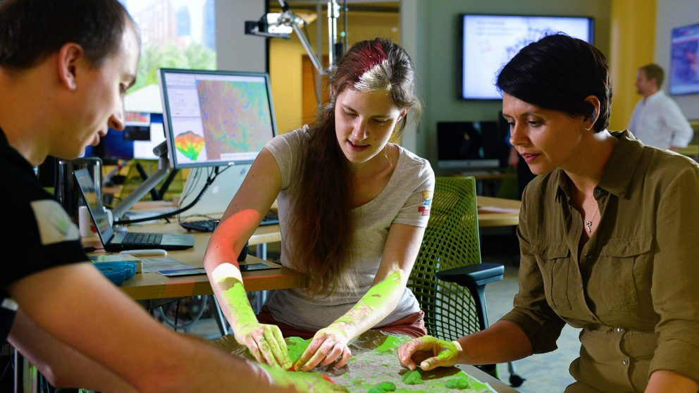 A photo of people using the Tangible Landscape at the North Carolina State University Center for Geospatial Analytics