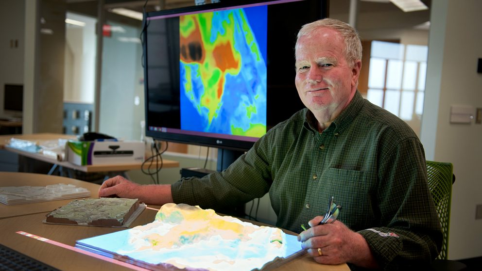 A photo of Hugh Devine using the Tangible Landscape at the North Carolina State University Center for Geospatial Analytics