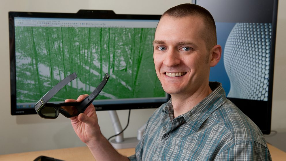 A photo of Zac Arcaro in the visualization lab at the North Carolina State University Center for Geospatial Analytics