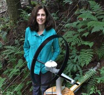A photo Laura Belica using pyranometers to measure solar radiation in a forest.