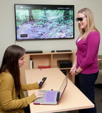 An image of two women conducting a geospatial 3-D visualization