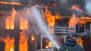A firefighter douses a house fire