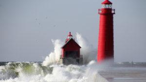 large waves crash against a lighthouse