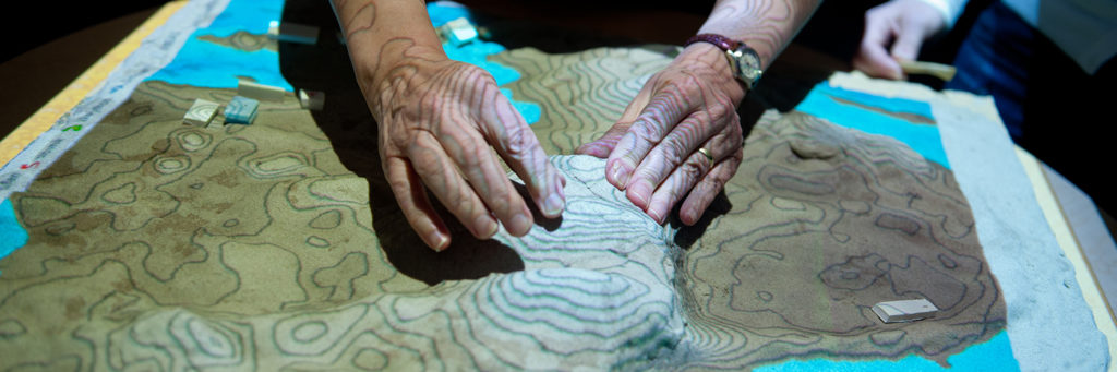 hands mold kinetic sand on Tangible Landscape
