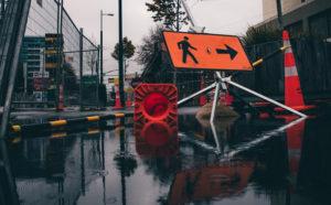 a pedestrian detour sign points around construction on wet pavement