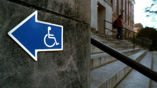 a sign points to a wheelchair accessible entrance near a set of stairs
