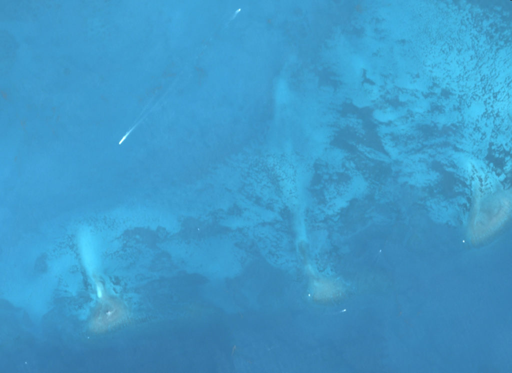 satellite image of ocean with small boats visible