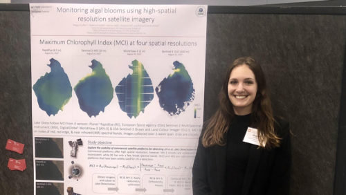 Megan Coffer stands with her research poster