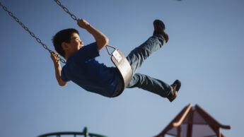 a child enjoys swinging on the swing set of a playground