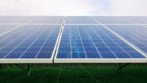 solar panels built on the ground point skyward, with grass below and blue sky above