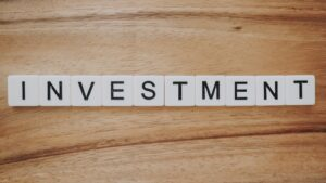 """block letters on a wood tabletop spell out the word """"investment"""""""