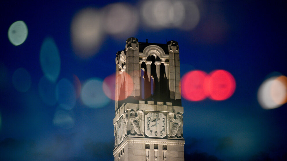 The NC State Belltower at dusk with colorful lights reflected around it