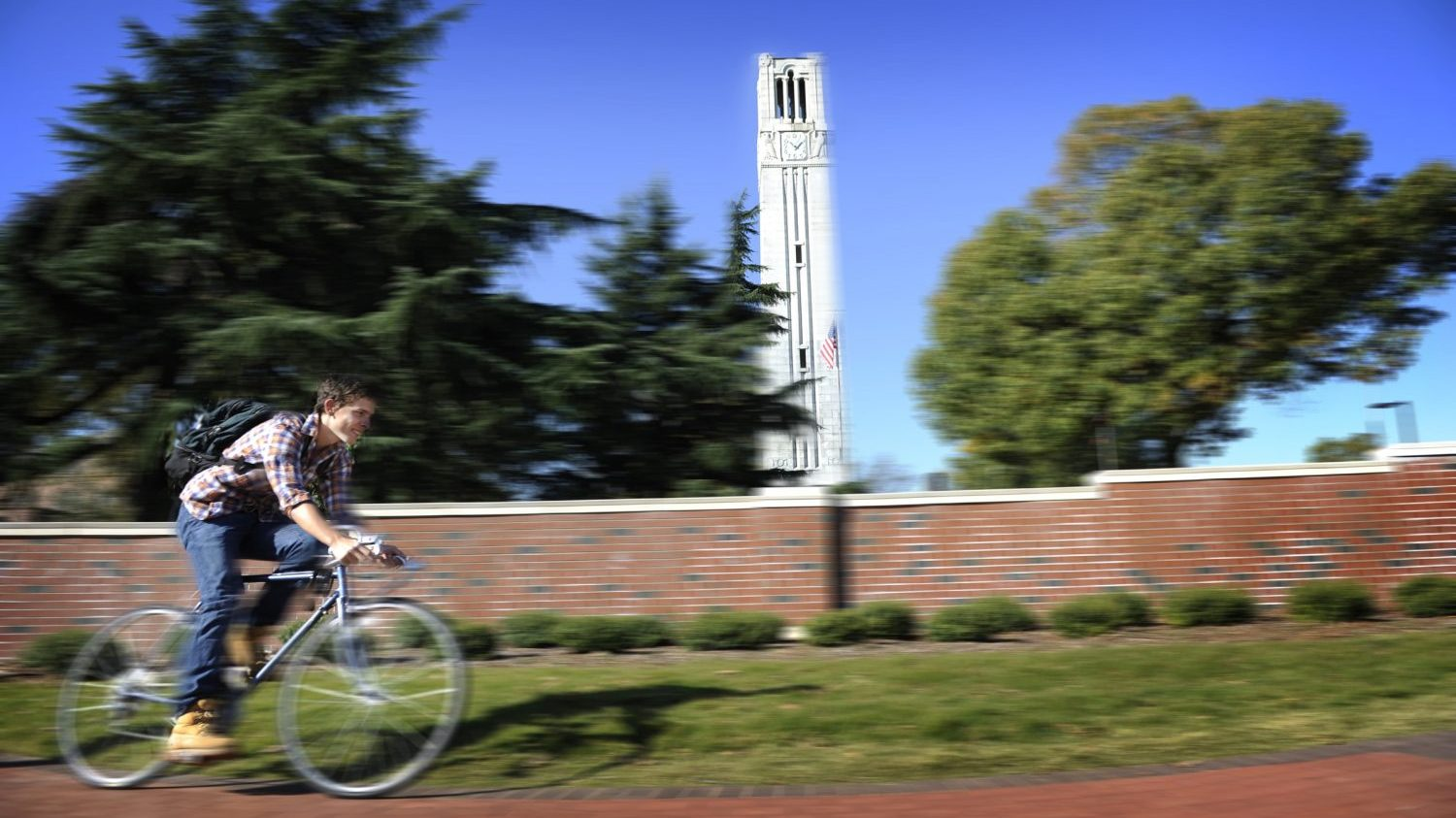 A student rides his bike by the Belltower.