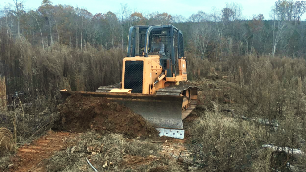 Forest Management major Rachel Burris driving a bulldozer as part of the CNR Work Crew
