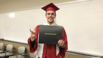 Ryan Held holding diploma after graduation ceremony