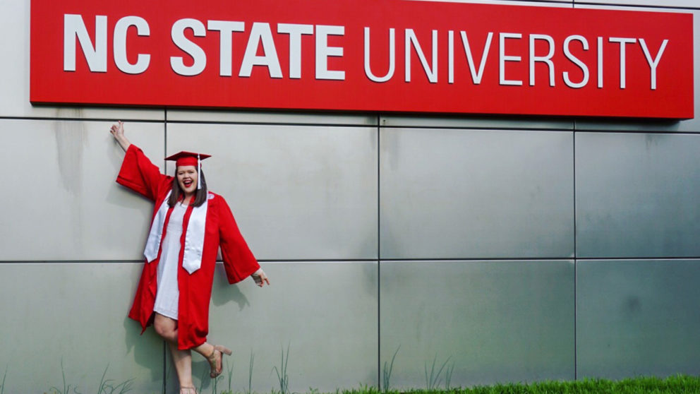 Student in front of NC State sign