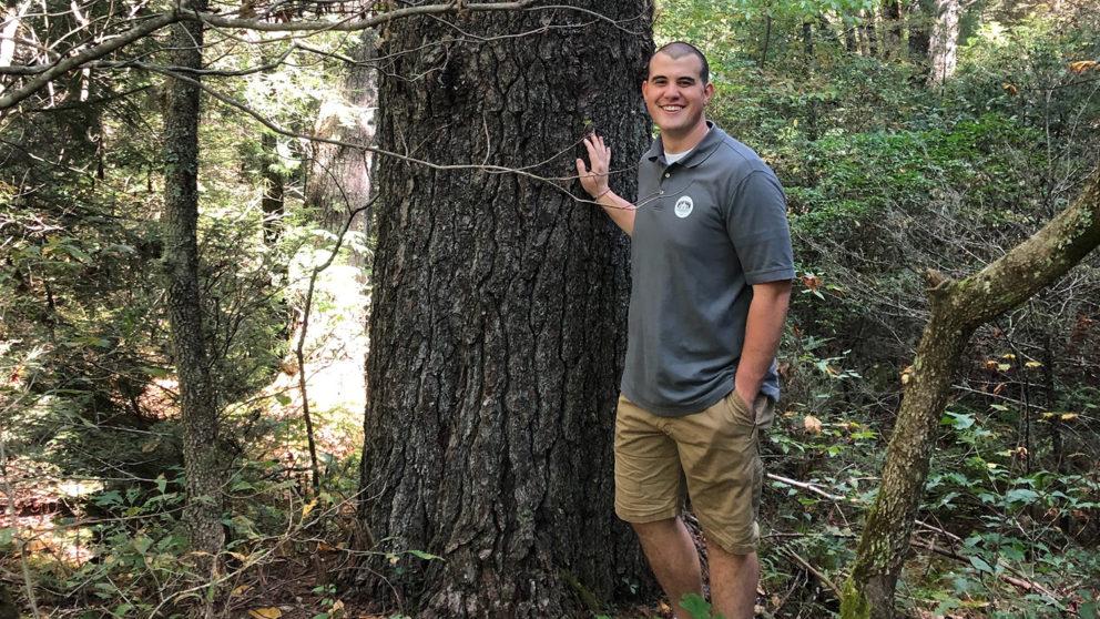 Student posing in field by tree