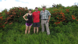 Students pose with faculty in field