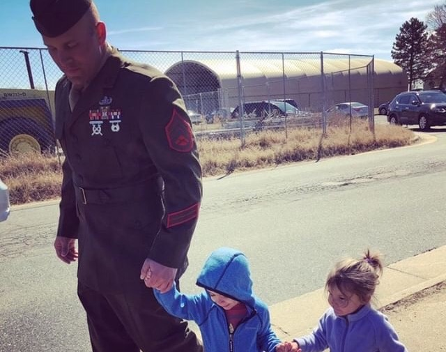 Student walks with kids in military uniform