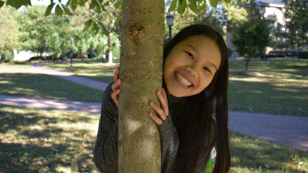 Student poses next to tree