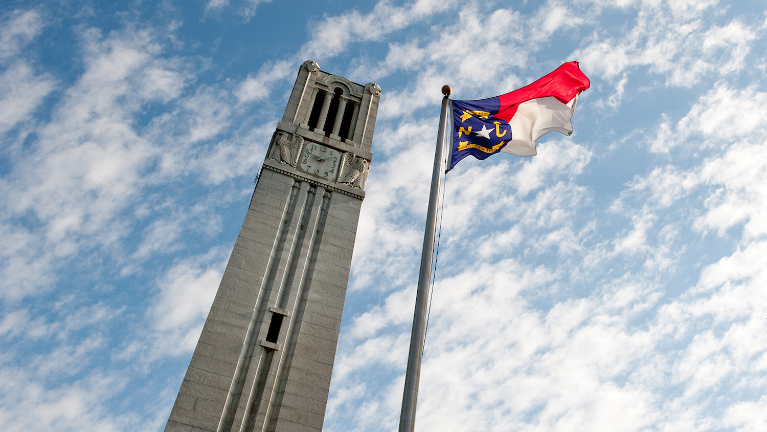 North Carolina flag flies beside by the NC State Belltower
