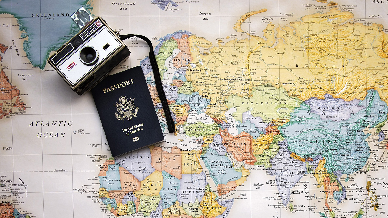 Passport and camera on top of a map