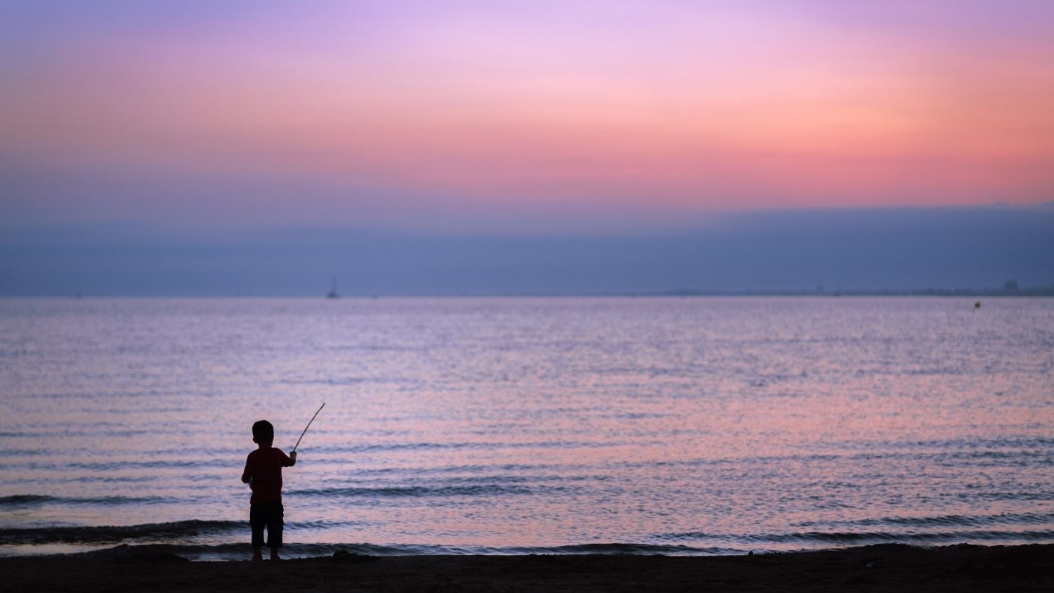 Silhouette of a child fishing.