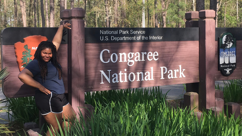 Roslynn poses in front of Congaree National Park sign
